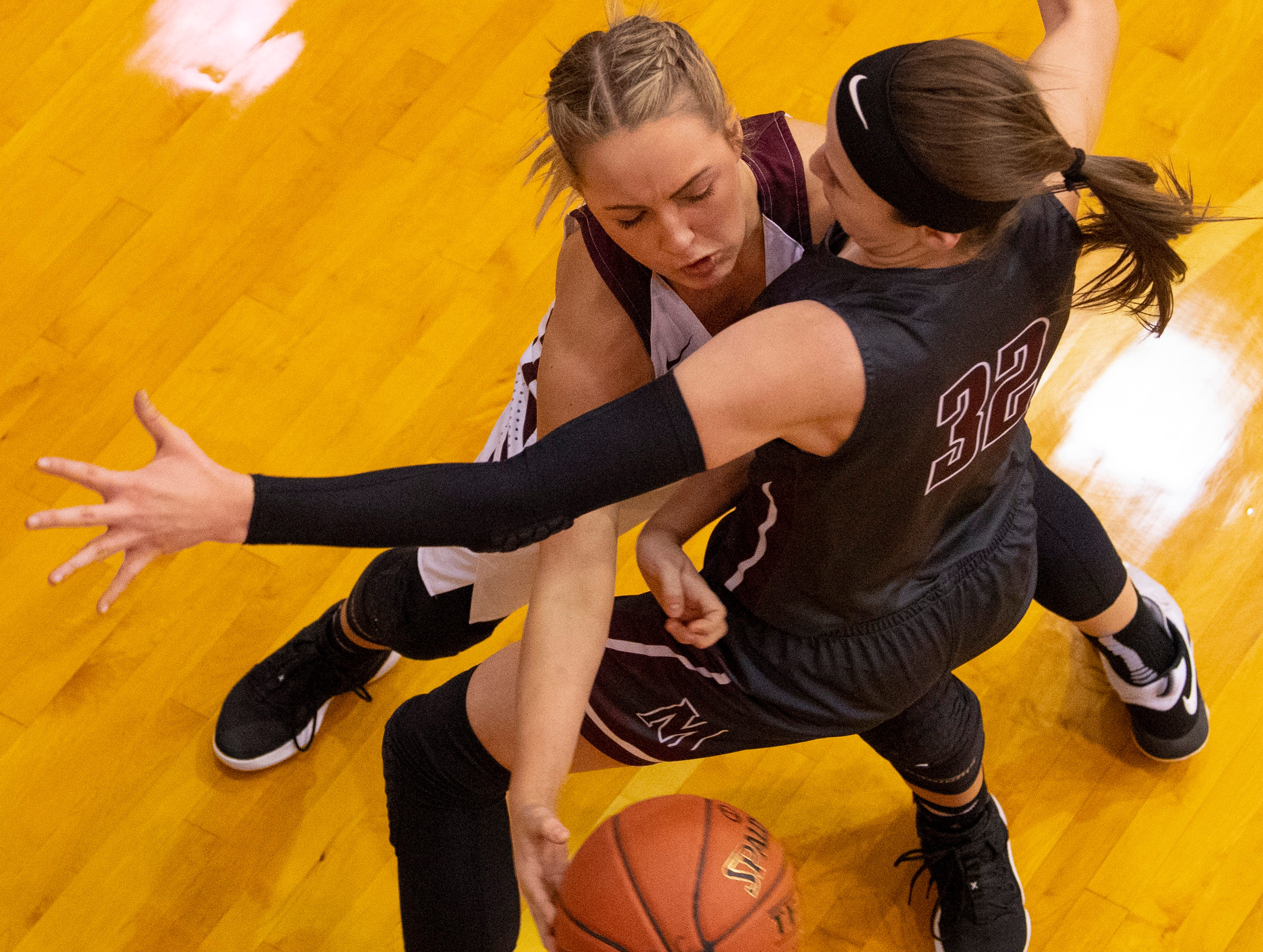 Henderson County's Savannah Lacer (4) passes around Madisonville's Lindsey Peyton (32) during the Girls Region Tournament semifinals at the Rocket Arena in Marion, Ky., Monday night.