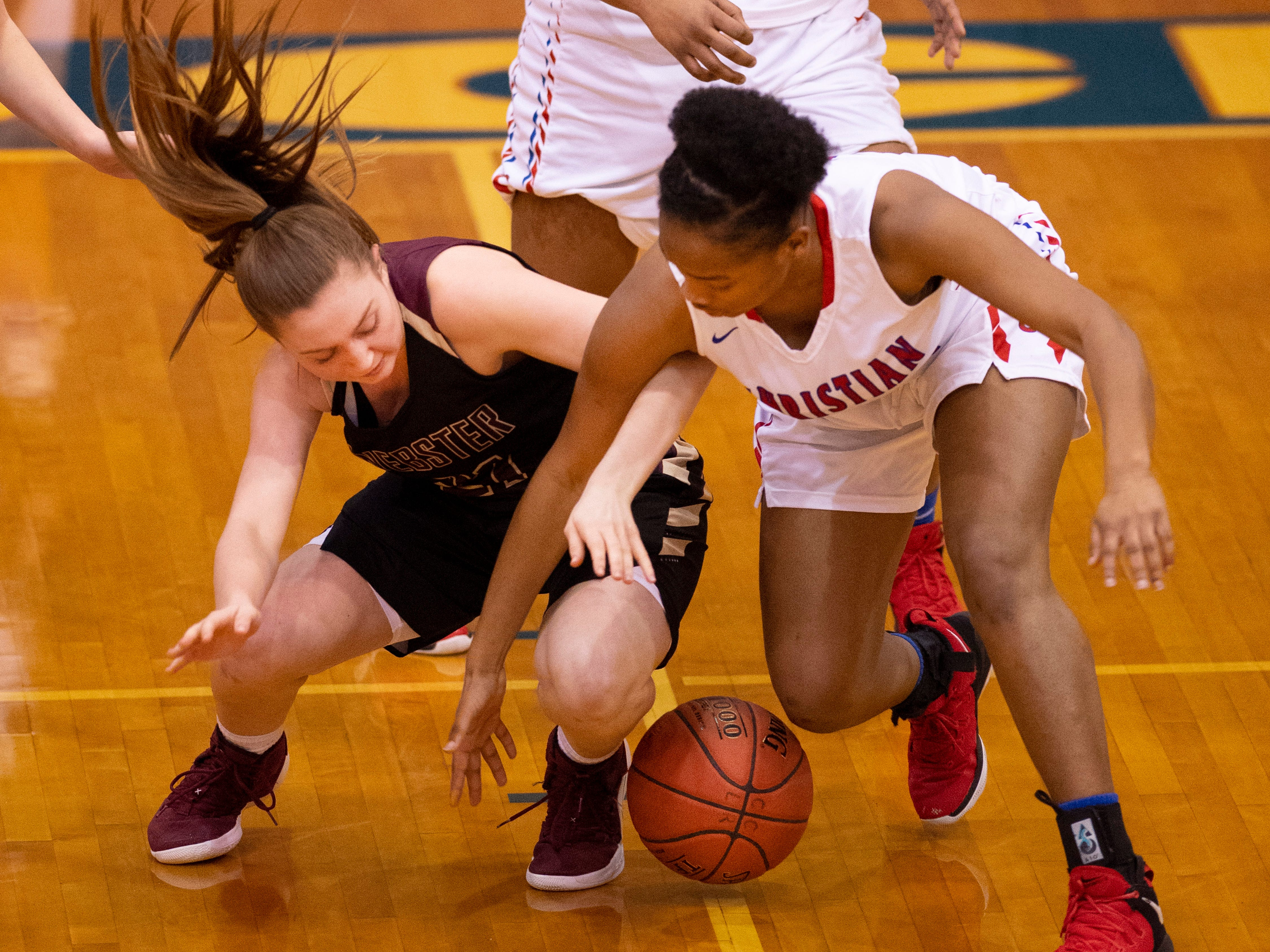 Webster County's Mariah Austin (21) and Christian's Eniya McGee (12) go for the ball during the Girls Region Tournament semifinals at the Rocket Arena in Marion, Ky., Monday night.