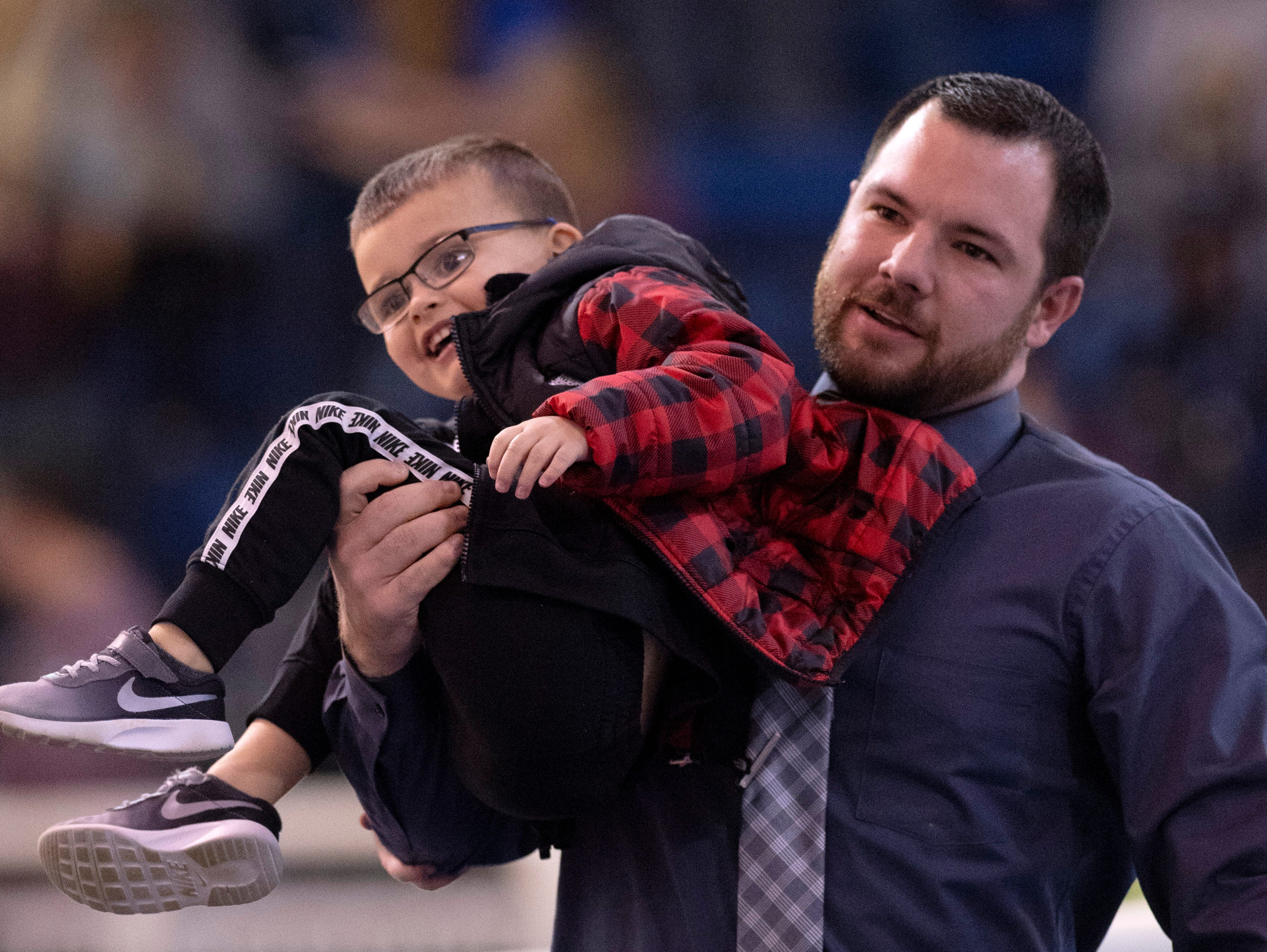 Cory Coble, Trigg County's basketball coach, returns his son, Owen, 4, to his mom after the youngster made a break between games at the Girls Region Tournament semifinals at the Rocket Arena in Marion, Ky., Monday night.