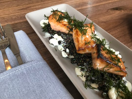 Crispy fried fennel fronds garnish salmon atop black quinoa and goat cheese  cream at LouVino on Mass Ave., Indianapolis.