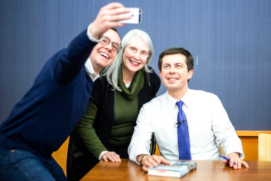 Druet Cameron Klugh, center, has her photo taken by Chasten Buttigieg, left, with his husband Pete Buttigieg, Mayor of South Bend, Indiana and 2020 Democratic presidential candidate, during an event on Monday, March 4, 2019, at the Public Library in downtown Iowa City, Iowa. Druet Cameron Klugh works as a librarian at the University of Iowa Law School.