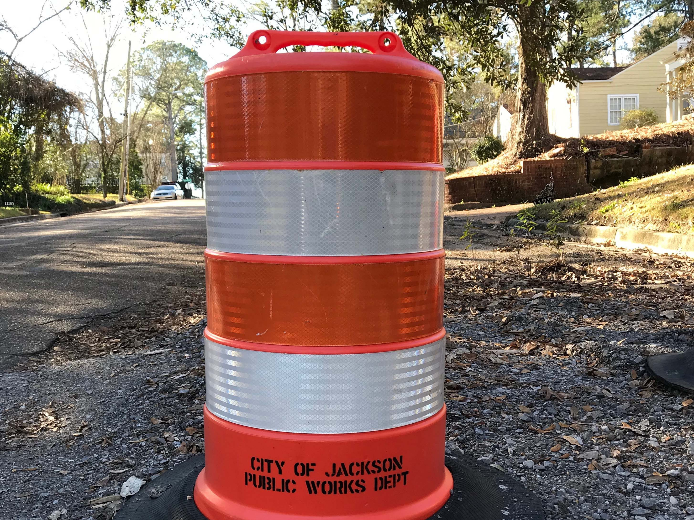 A City of Jackson Public Works Department barrel sits atop unfinished road patching on Quinn Street in the Belhaven neighborhood of Jackson, Miss. The road has suffered multiple water main breaks and a bridge on the street is falling into a creek running beneath the street. Thursday, January 10, 2019