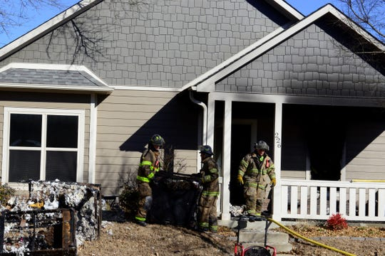 Firefighters carry charred furniture out of a Wells Street house in downtown Jackson as they search for the cause of the fire Tuesday afternoon.