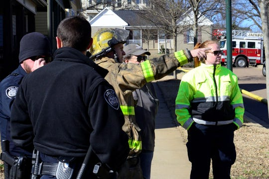 A firefighter explains house damage to the homeowner after a downtown Jackson residence caught fire Tuesday afternoon.