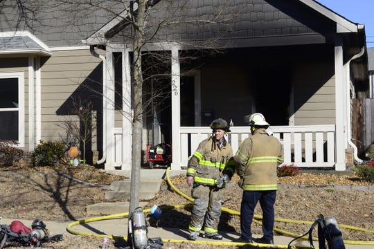 A firefighter talks to Battalion Chief Christopher March in front of a burned residence in downtown Jackson on Tuesday afternoon.