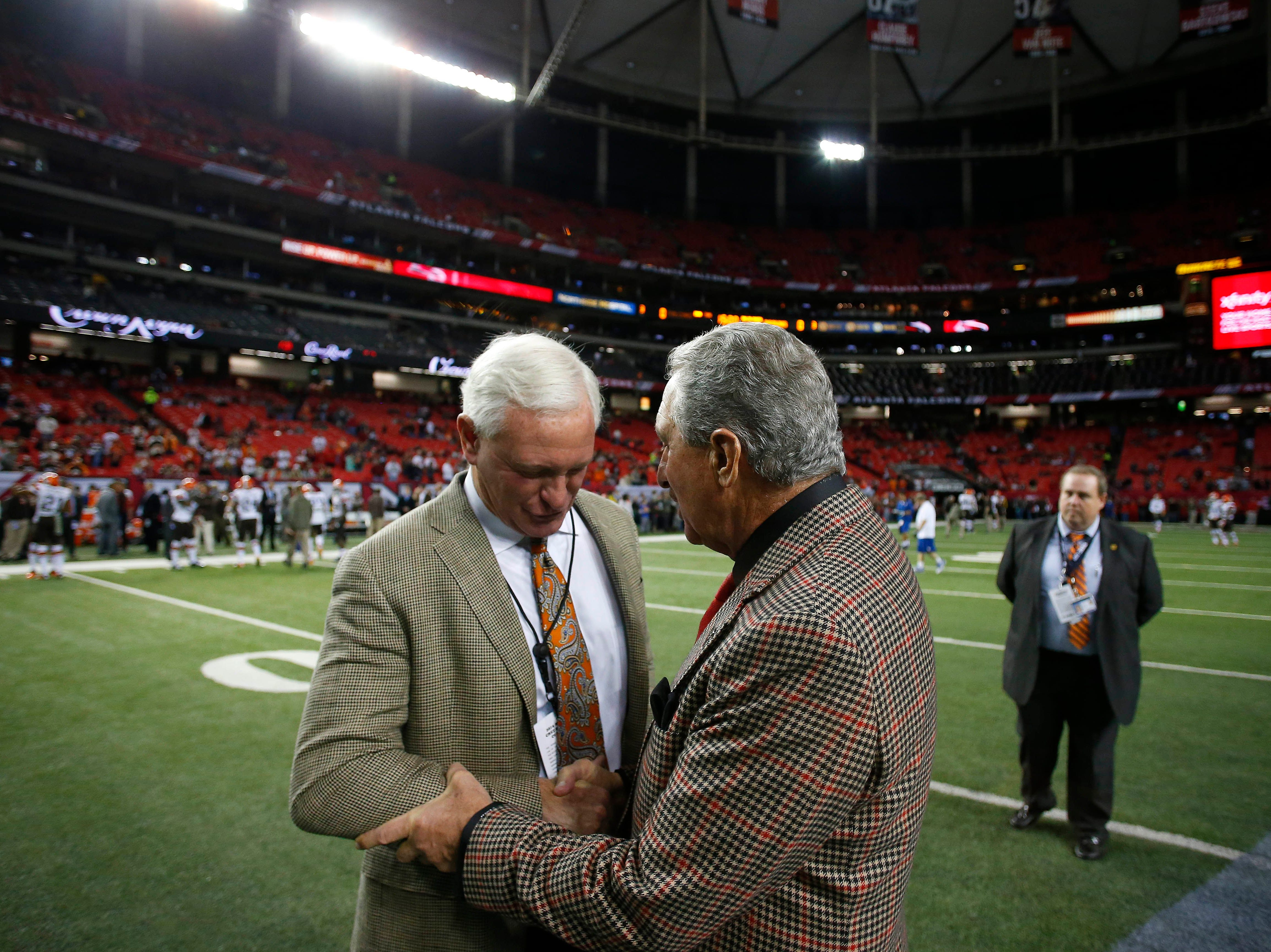 Cleveland Browns owner Jimmy Haslam, left, greets Atlanta Falcons owner Arthur Blank during the first half of an NFL football game, Sunday, Nov. 23, 2014, in Atlanta.
