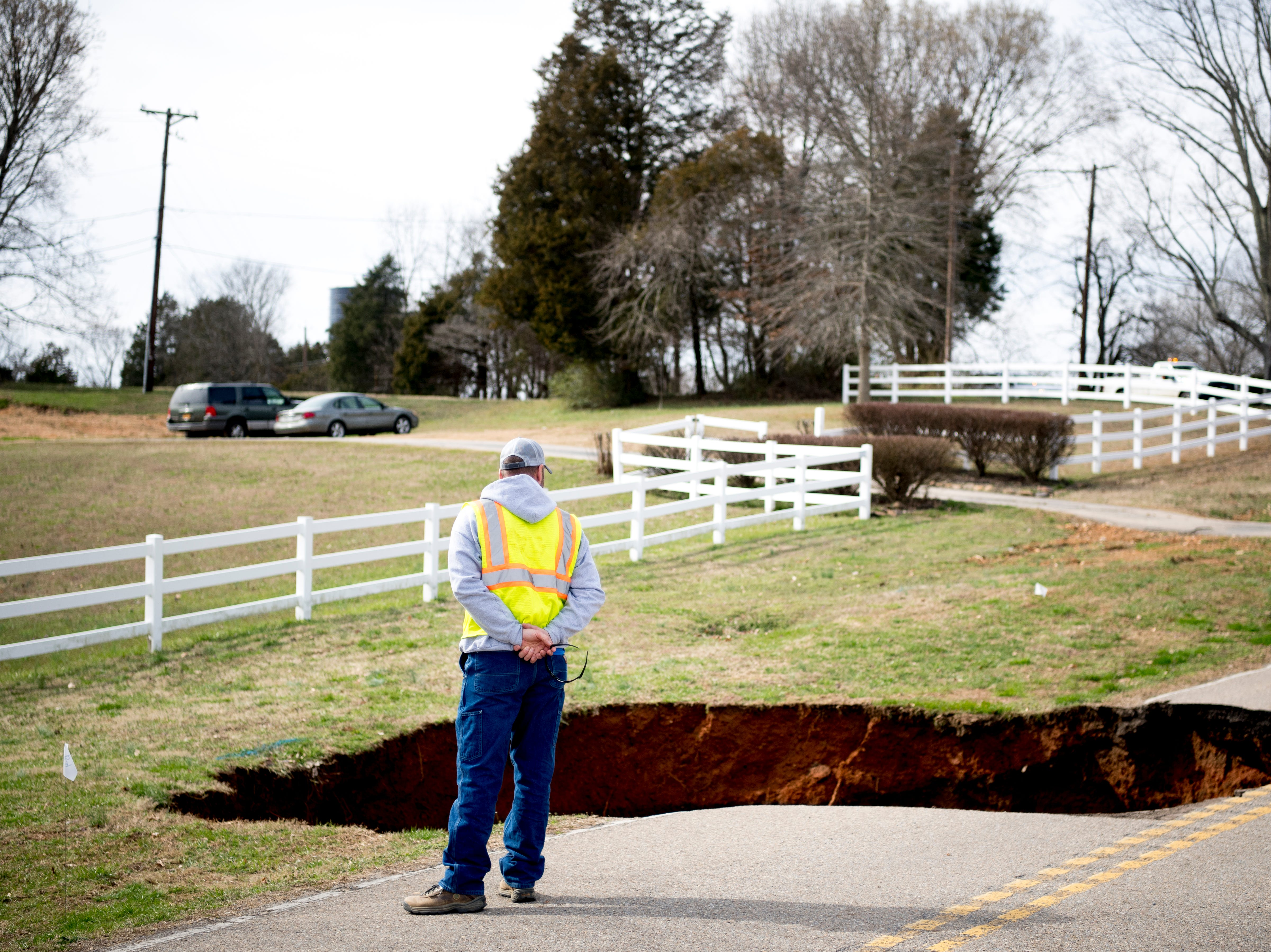 Travis Farmer, with Hallsdale-Powell Utility District, gets a better view of a large sinkhole on Greenwell Road in Powell, Tennessee on Tuesday, February 26, 2019. The sinkhole is estimated to be around 20 feet deep.