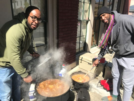 Darrell Benjamin, left, and Phillip Jean-Louis stir up some white beans and gumbo for family and friends and anyone else who drops by.