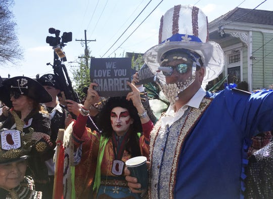 Costumed revelers gather Monday, March 4, 2019, for the annual Krewe of Red Beans march in New Orleans. The usually lighthearted parade began with a funeral dirge by a brass band in memory of Sharree Walls, a krewe member who was one of two killed when a car veered into a bike lane Saturday night.