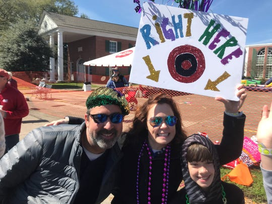 Curtis and Amanda Logue with one of their children enjoy throwing beads from a float as much as they like catching them.