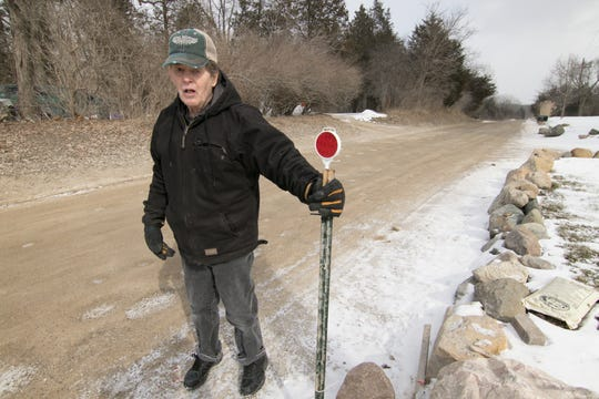 Terry Chuhran, shown Tuesday, March 5, 2019, stands at the surveyor's marker indicating the end of his property on McCabe Road in Green Oak Township. Chuhran says officials are trying to move McCabe Road onto his property.