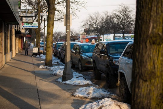 Cars are parked along East Michigan Avenue on Lansing's east side between Fairview and Clemens avenues on Monday, March 4, 2019. New businesses have made parking challenging.