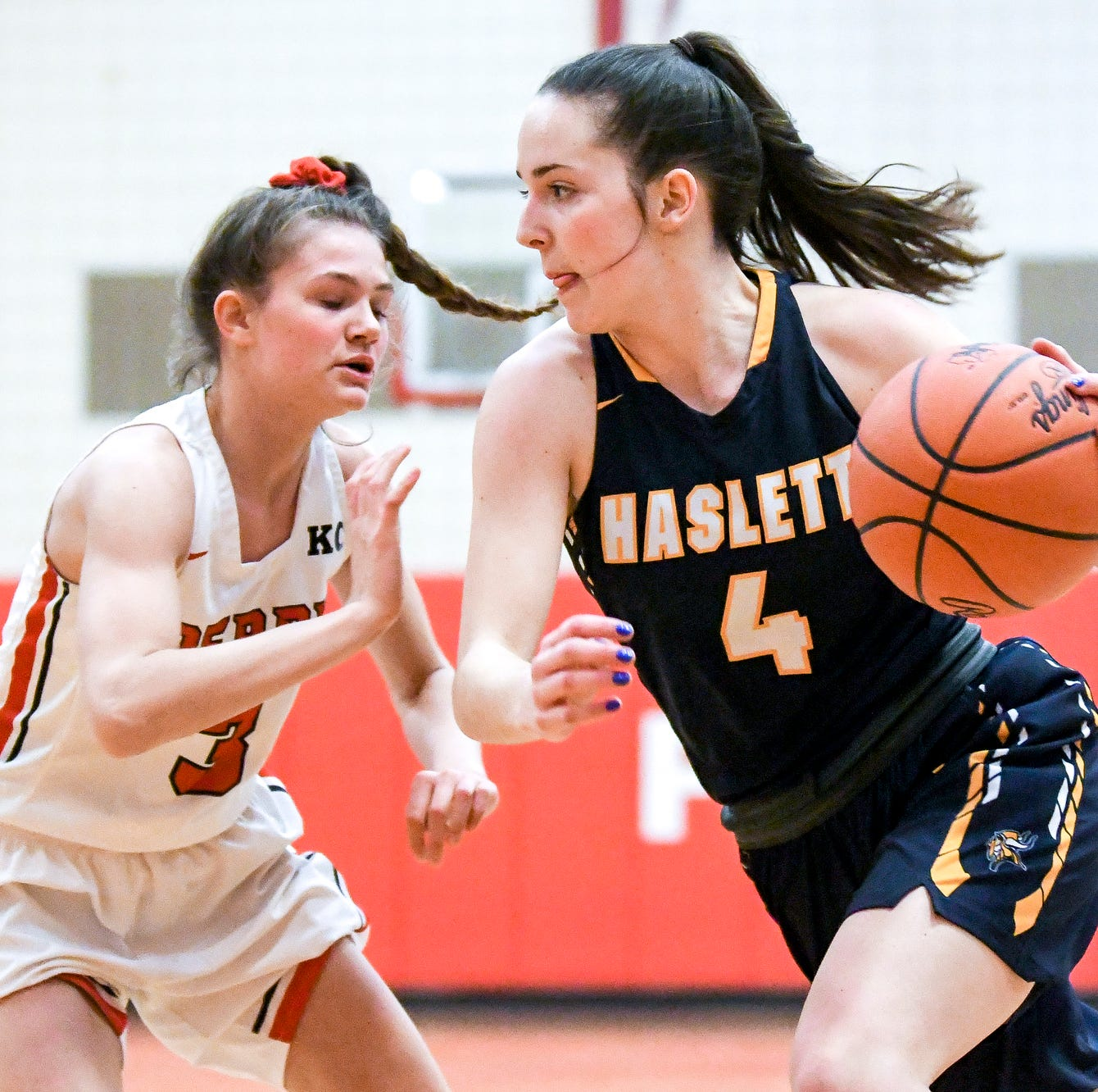 Haslett's Ella McKinney, right, moves past Perry's Elizabeth Gramza during the first half on Monday, March 4, 2019, at Perry High School.
