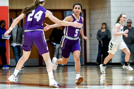 Fowlerville's Azhanae Depa, right, celebrates after making a 3-pointer with teammate Elie Smith during the fourth quarter on Monday, March 4, 2019, at Perry High School.