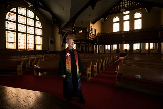 Rev. Mark Thompson, an openly gay pastor at Central United Methodist Church in Lansing, poses for a portrait in the church sanctuary, Monday, March 4, 2019.