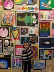 A Manitowoc public school student proudly points to his artwork on display at the Rahr-West Art Museum for the month of March.