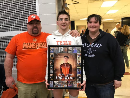 Mansfield Senior state qualifier Josh Lyons with his parents, Matt and Kristina, after recording victory No. 100 in his final match at the Division II district tournament in Norwalk.