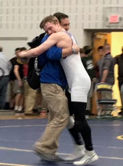 Ontario freshman Ethan Turnbaugh hugs his father, Wes, after winning a Division II district wrestling championship last weekend in Norwalk.