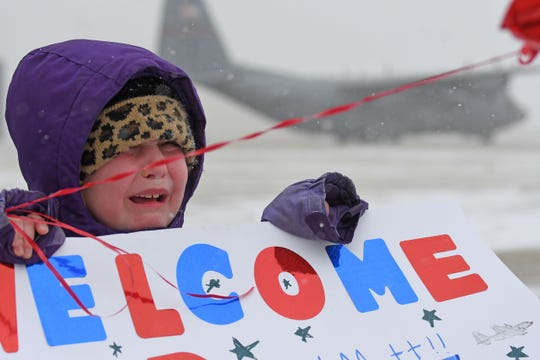 Ella Wilson of Oklahoma is overcome with excitement and cold Tuesday afternoon as she waits to greet her father, Capt. Darryl Wilson, the pilot of the C-130 that carried about 30 military personnel back from deployment in the Middle East.