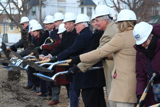 Richard Harding Sr., center right, in tan, tosses dirt into the air at a ground-breaking ceremony for the Warren G. Harding Presidential Center, what is expected to be a roughly 12,000-square-foot museum.