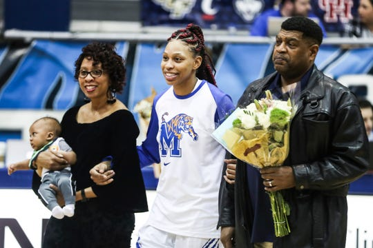 Ashia Jones, center walks onto the court with her parents, Angel and Wesley Jones, and son, Timmy Jr., during senior night celebrations before the start of Monday night's game against Temple.