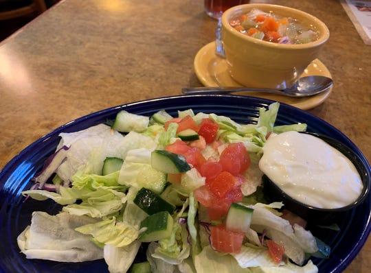 A salad, foreground, and cup of chicken soup from Mel's Diner, Golden Gate.