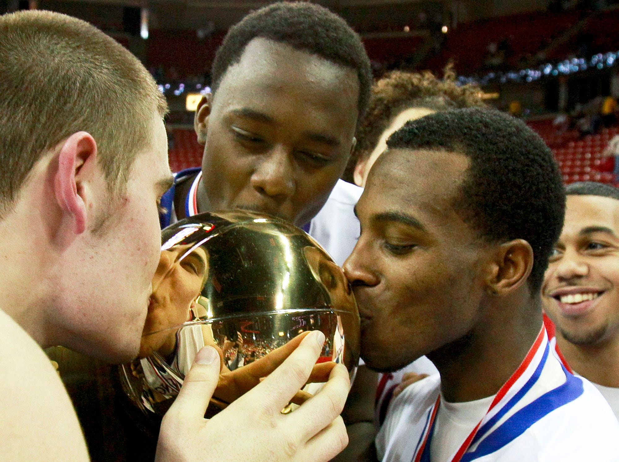 Wisconsin Lutheran's Andrew Rumler, left, Flavien Davis, center, and Cedquon Holmes all kiss the 2009 Division 2 championship trophy after beating Monroe 79-67 in a basketball game at the WIAA state tournament.