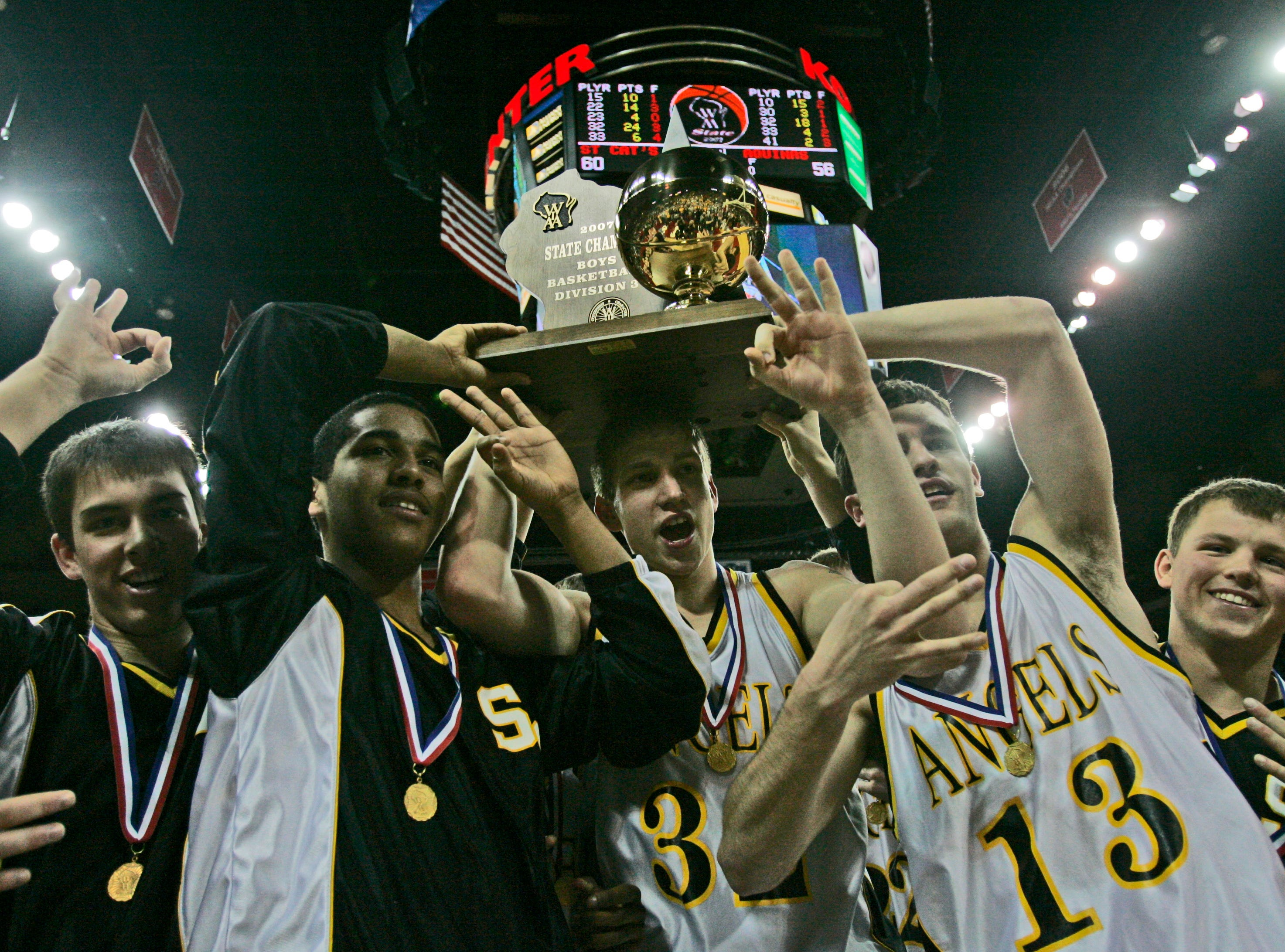 Racine St. Catherine's Angels' hold the championship trophy after their 60-56 win over Lacrosse Aquinas Bluegolds in the 2007 Division 3 WIAA State Basketball Tournament Finals, being held at the Kohl Center in Madison.