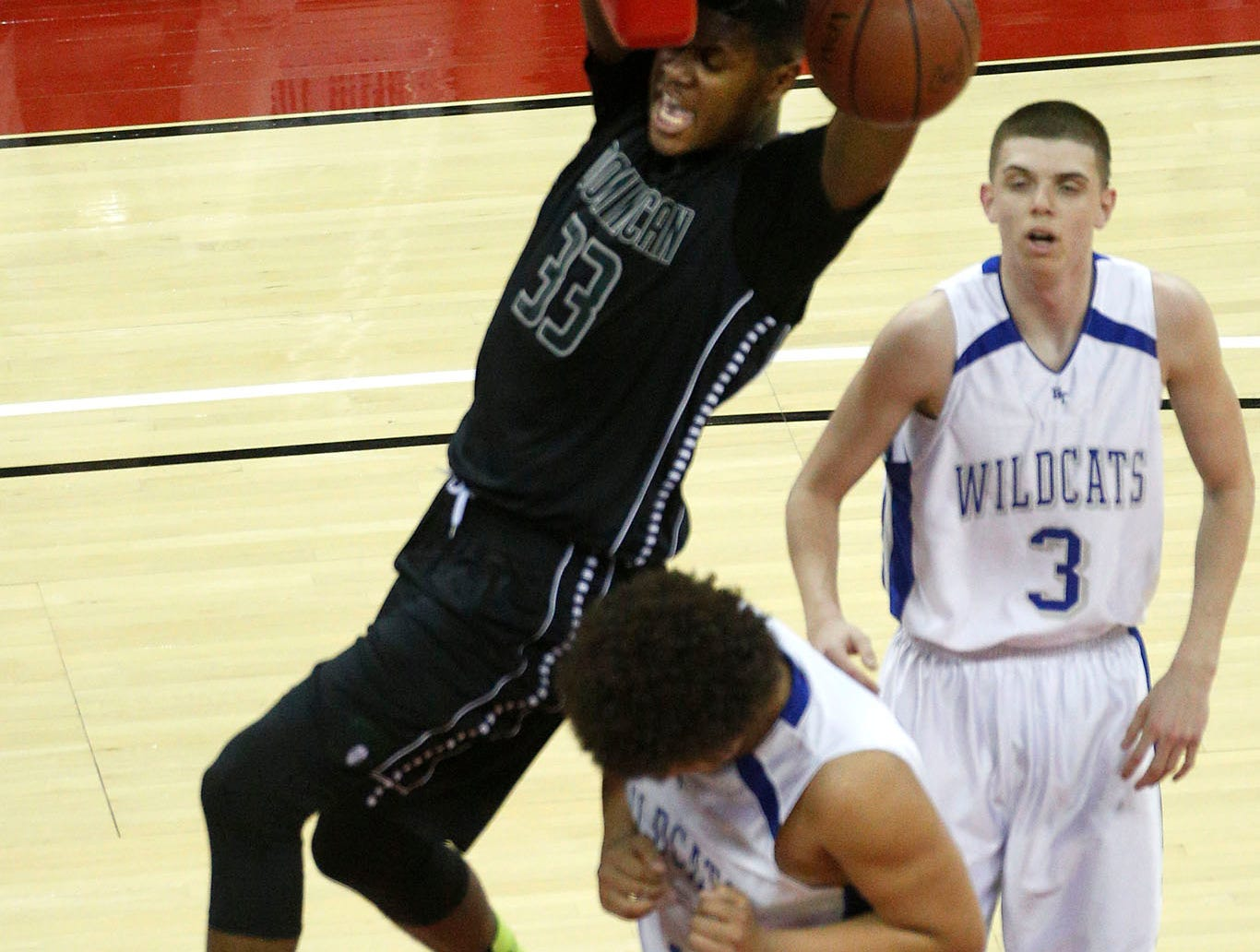Dominican's Diamond Stone hangs from the rim after dunking over Blare-Taylor's River Kirchner as Dalton Soto looks on during the second half of the teams W.I.A.A Division 4 Boys State Basketball Tournament Championship game against Neenah in the Kohl Center Saturday, March 14, 2014.