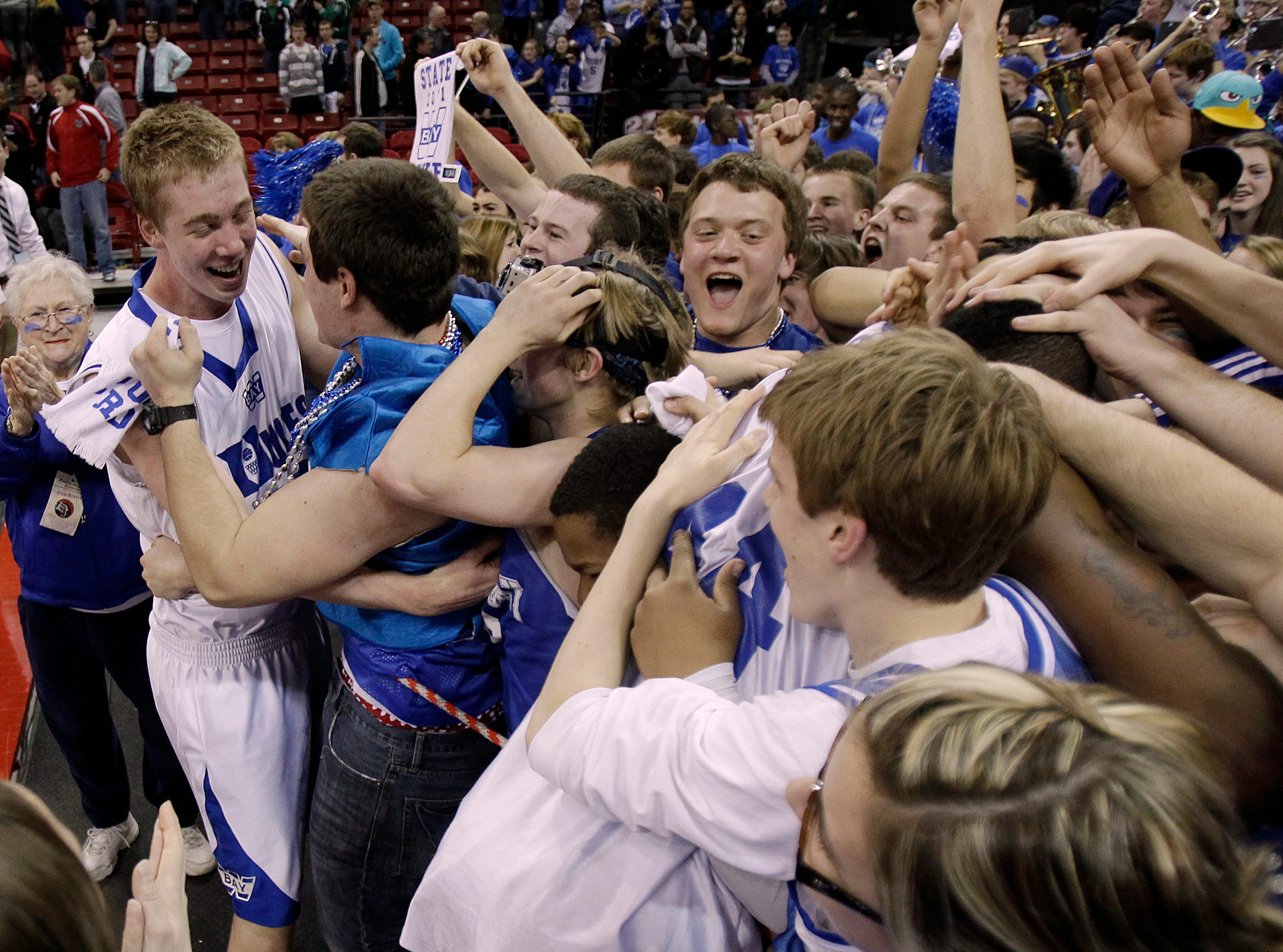 Whitefish Bay's Jamie Schneck is greeted by fans after beating  Seymour  during the 2011 WIAA state basketball tournament at the Kohl Center.