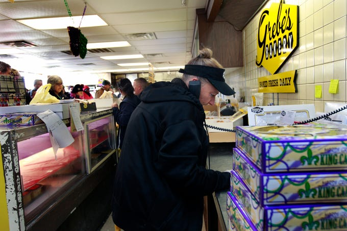 While customers line up for paczki, Chris Rische take orders over the phone at Grebe's Bakery in West Allis. Grebe's has been making paczki from scratch since 1937 and expects to sell 70,000 Tuesday. The favorite seller is the prune.