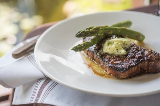 A prime-aged New York strip is served with chef's butter and asparagus at Del-Bar supper club in Wisconsin Dells.
