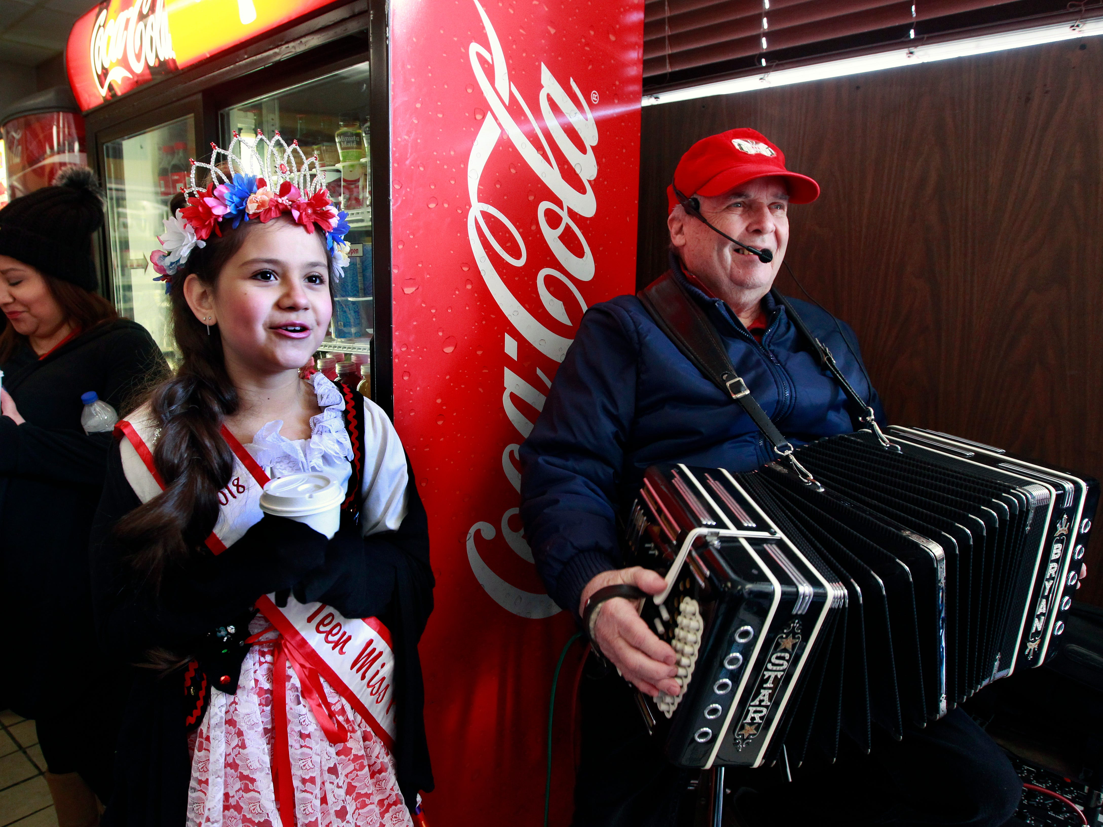 "Isidra Malkowski, Pre-Teen Miss Polish Festival (center), and Bryan O'Donnell  lead customers in the song ""Beer Barrel Polka"" -- or better known as ""Roll Out the Barrel"" -- at Grebe's Bakery for customers waiting for their paczki orders."
