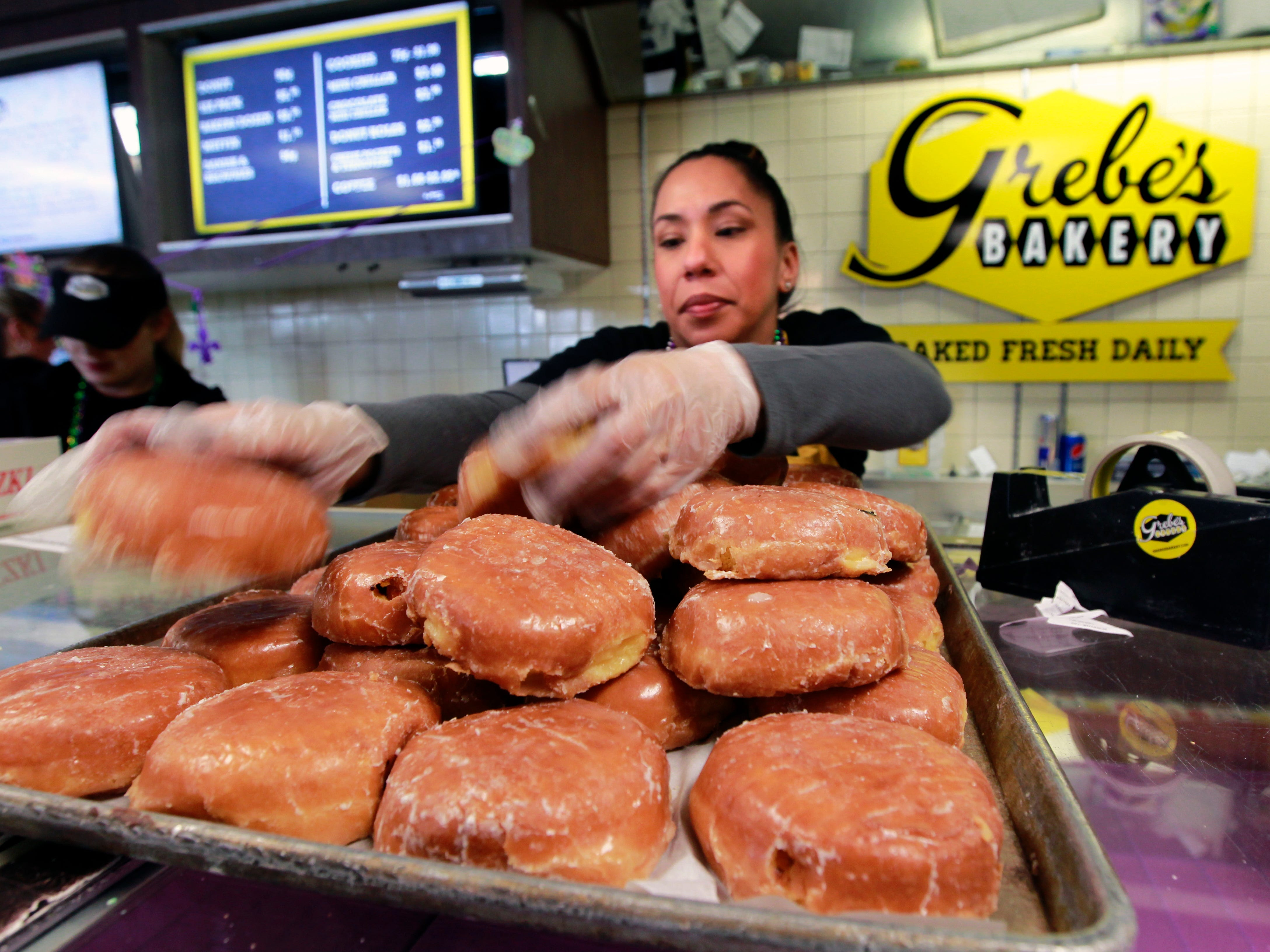Tanya Aguirre restocks a prune paczki tray for customers at Grebe's Bakery in West Allis.