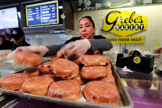 Tanya Aguirre restocks a prune paczki tray for customers at Grebe's Bakery in West Allis in 2019.