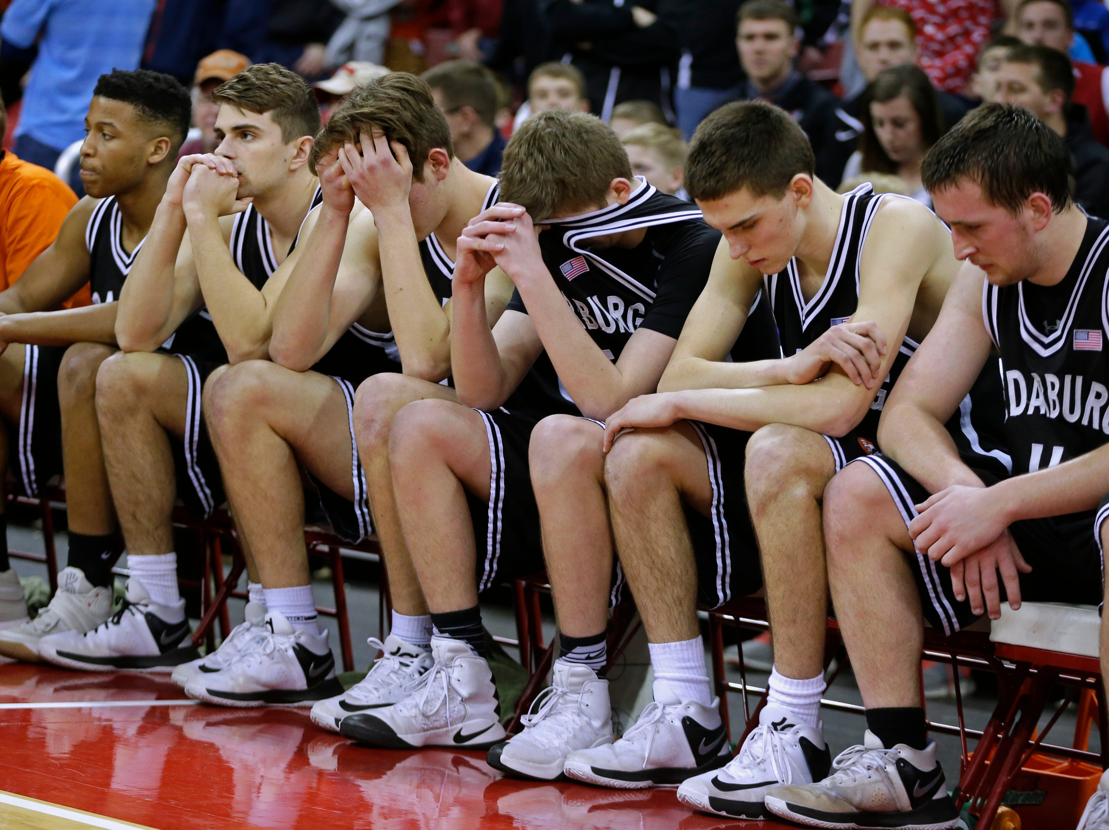 Cedarburg teammates are somber after their 55-53 loss to La Crosse Central in the 2017 Division 2 Championship  game at the WIAA boys' state basketball championships.