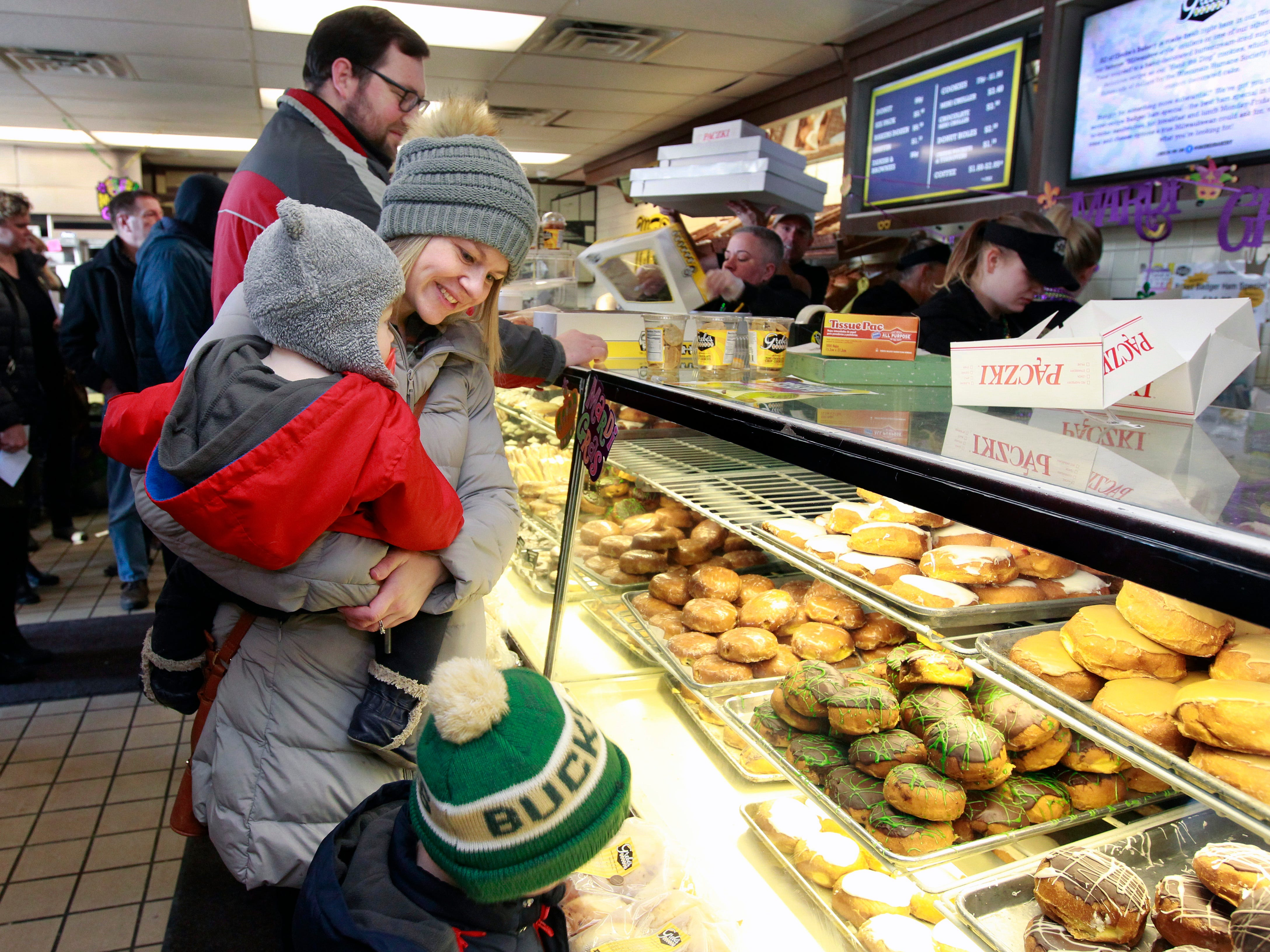 "Laura Folger of Milwaukee holds son Oliver, 1, while she and son Dylan, 3, make their selection for paczki at Grebe's Baker in West Allis. Instead of doing errands on her day off, she decided to pick up a half-dozen custard flavor. ""Theirs are the best I've ever had,"" Folger said."