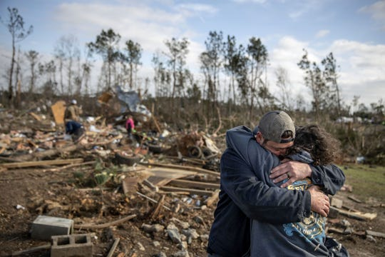 Carol Dean, right, is embraced by David Theo Dean as they sift through the debris of the home Carol shared with her husband and David's father, David Wayne Dean, who died when a tornado destroyed the house in Beauregard, Ala., Monday, March 4, 2019.