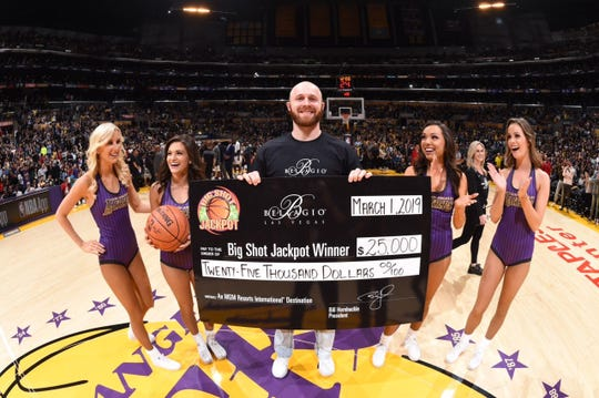 Logan Thomas, a 2011 Monroe Central grad, poses at midcourt after hitting a halfcourt shot at the Los Angeles Lakers game on March 1.