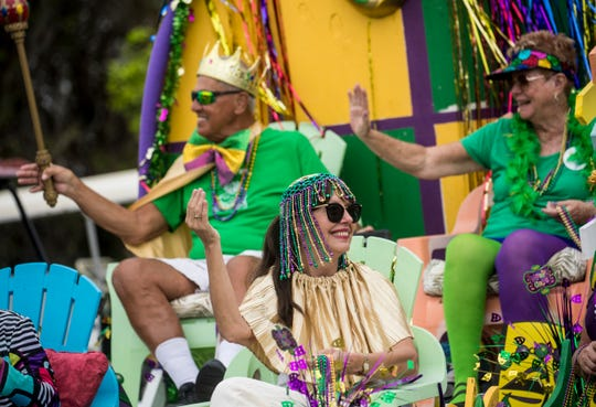 Tina Saberton, front, along with Lennie and Paul LeFevre take part in the 35th annual Mardi Gras parade at Citrus Park in Bonita Springs on Tuesday 3/5/2019.