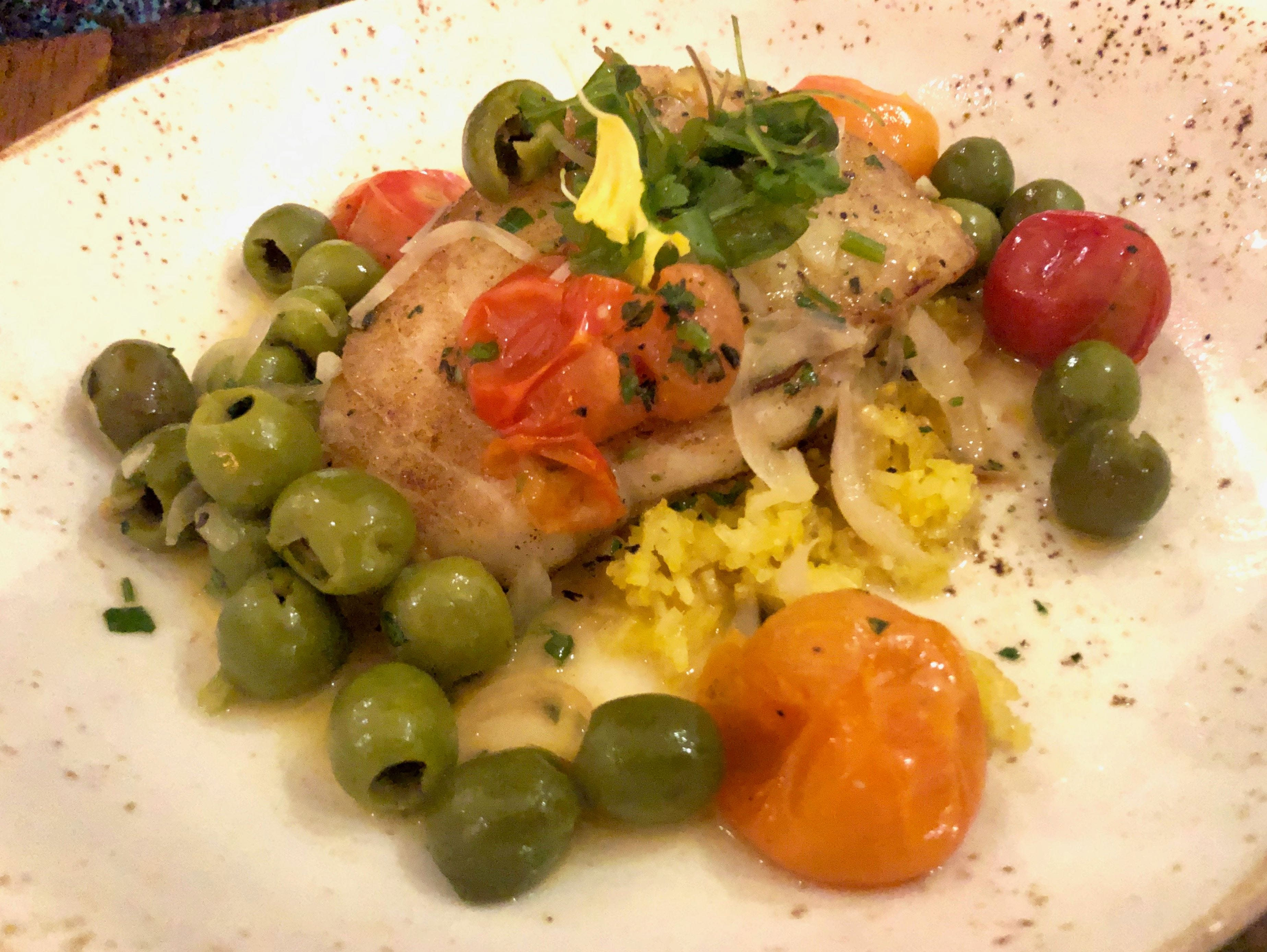 Chilean seabass is prepared Veracruz-style with Castelvetrano olives on a bed of saffron rice at Charred North in Bonita Springs.