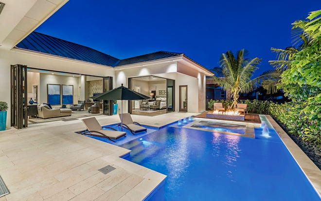 An elaborate pool with spa, wet shelf and several fire features is a design element found in many residences by KTS Homes.
