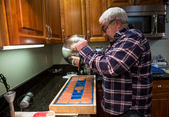 Charlie Kramer pours a soap mixture into the molds he created. Kramer, along with his wife 