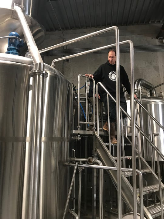 Ghost Hawk Brew Master Chris Sheehan atop of the tanks where the first batch began brewing on Tuesday.