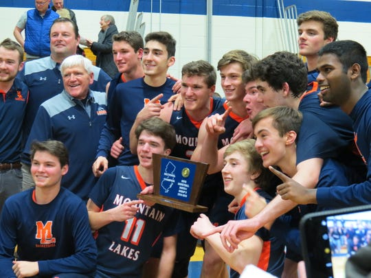 Mountain Lakes celebrates after winning the North 1, Group 2 boys basketball title with a 40-31 overtime win over defending champ Ramsey in Ramsey on Monday, March 4, 2019.