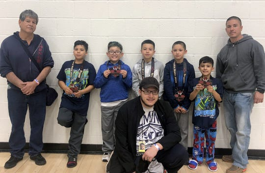Deming Youth Wrestling Club teammates returned from the state tournament in Rio Rancho with medals. Pictured from left are Head Coach Rumaldo Bencomo, Devyn Garces, Micah Guevara, Erik Bencomo (jr), Angel Bencomo, Dominic Garces and coach Erik Bencomo (sr). Pictured in front is coach Tony Guevara.