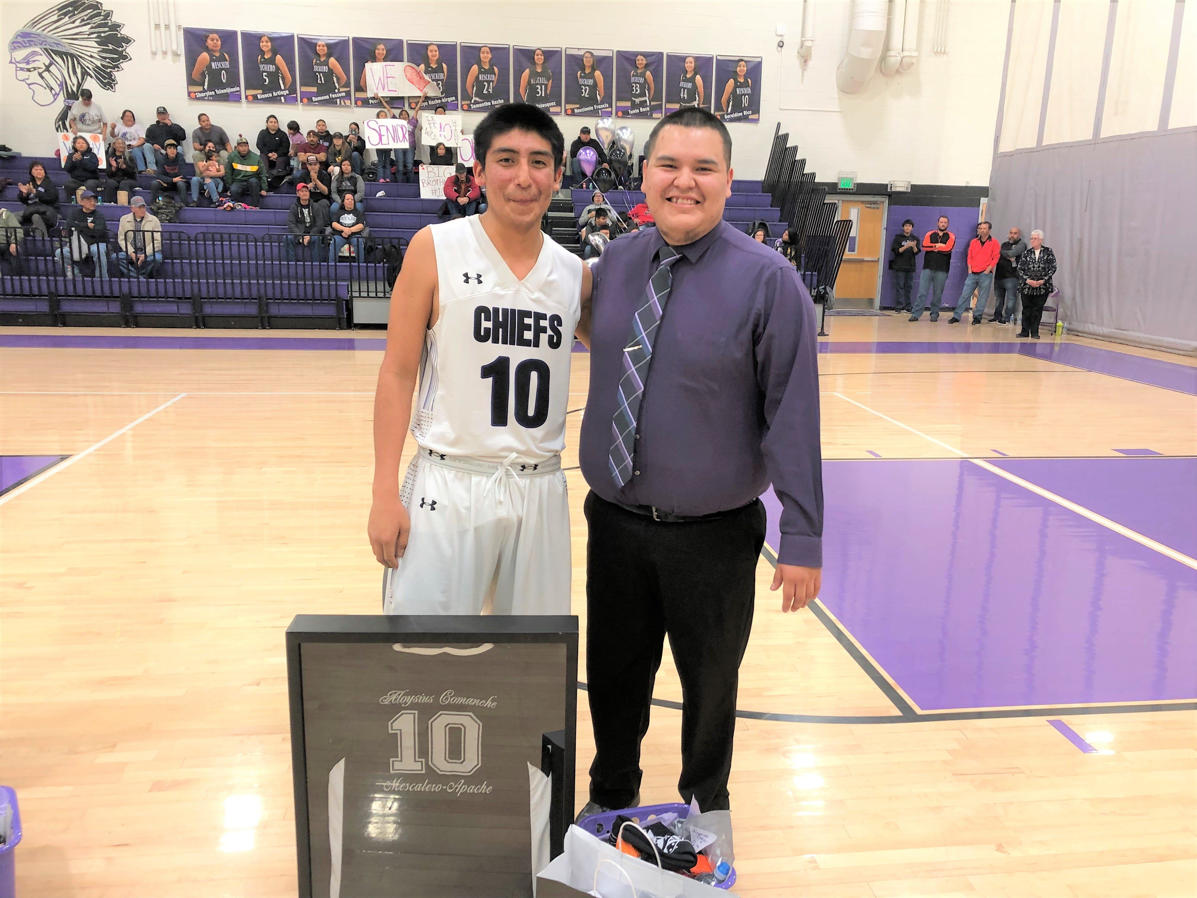 Aloysius Comanche #10 and Coach Kane show off their school spirit during a game at Mescalero Apache School. T