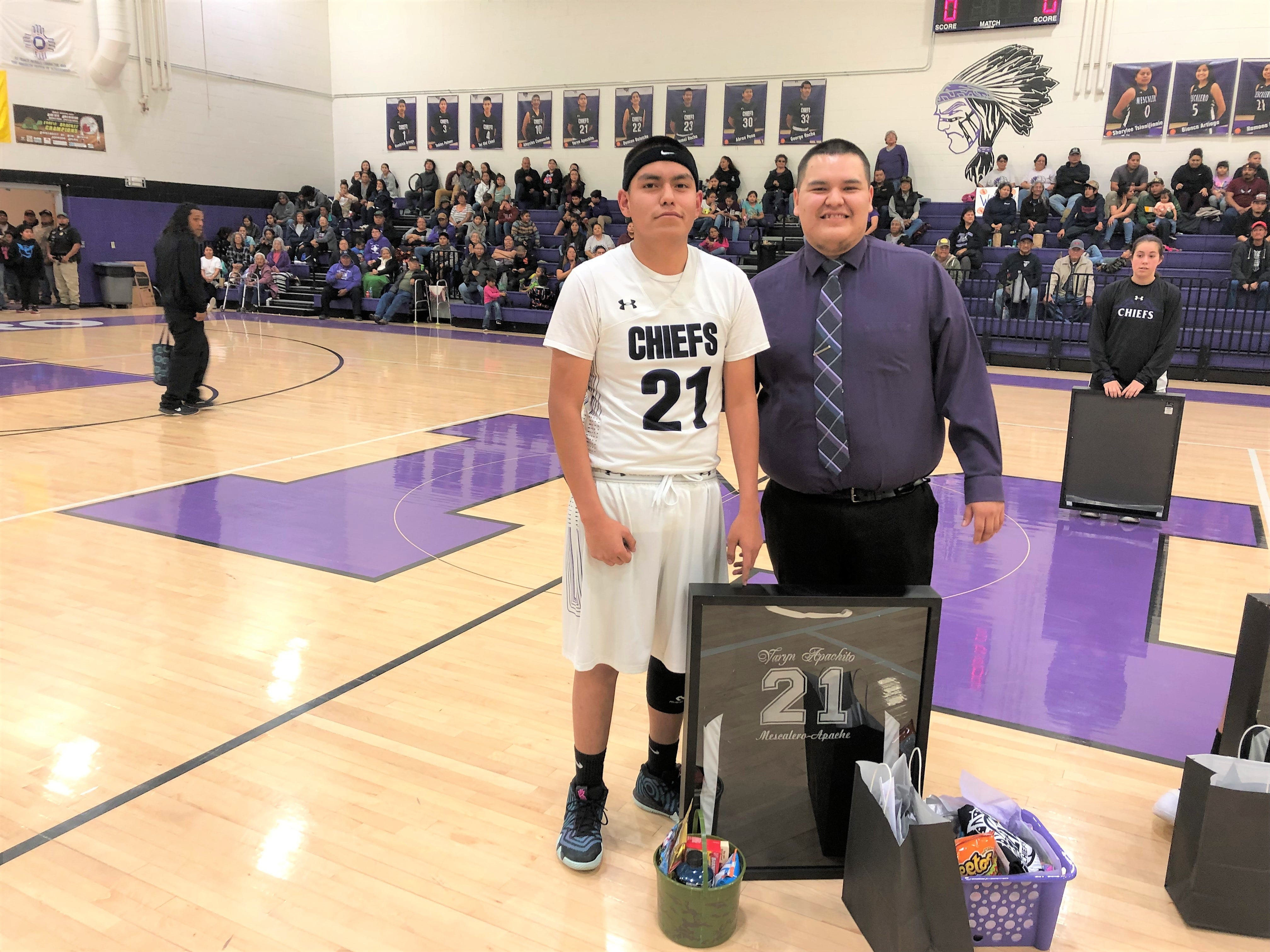 A varsity boys basketball player stands next to coach Kane with his newly framed jersey. The school celebrates both academic and athletic departments and is proud of their students.