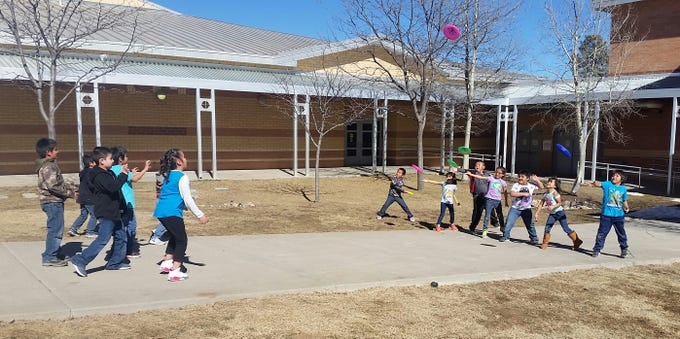 Mrs. Helmke's first grade class at Mescalero Apache School took advantage of the beautiful day and sunshine to play Frisbee in the courtyard. The playground had been covered for days with snow, and the students were excited to outside for a day of 'Fun in the Sun'.