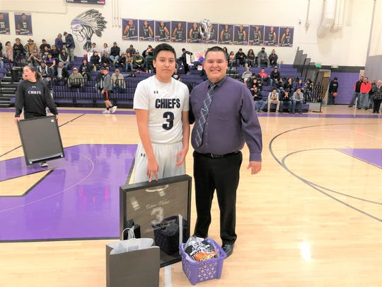Coach Kane of the Mescalero boys basketball;ll stands next to a senior varsity boys basketball player with his newly framed jersey.